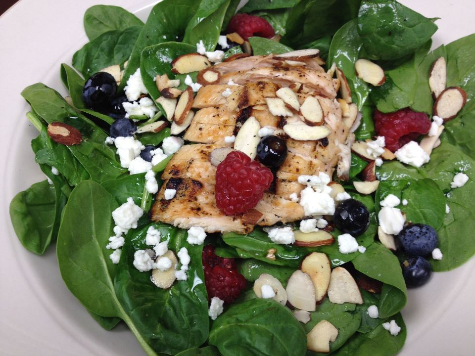 Grilled chicken over spinach with raspberries, blueberries, sliced almonds and feta cheese