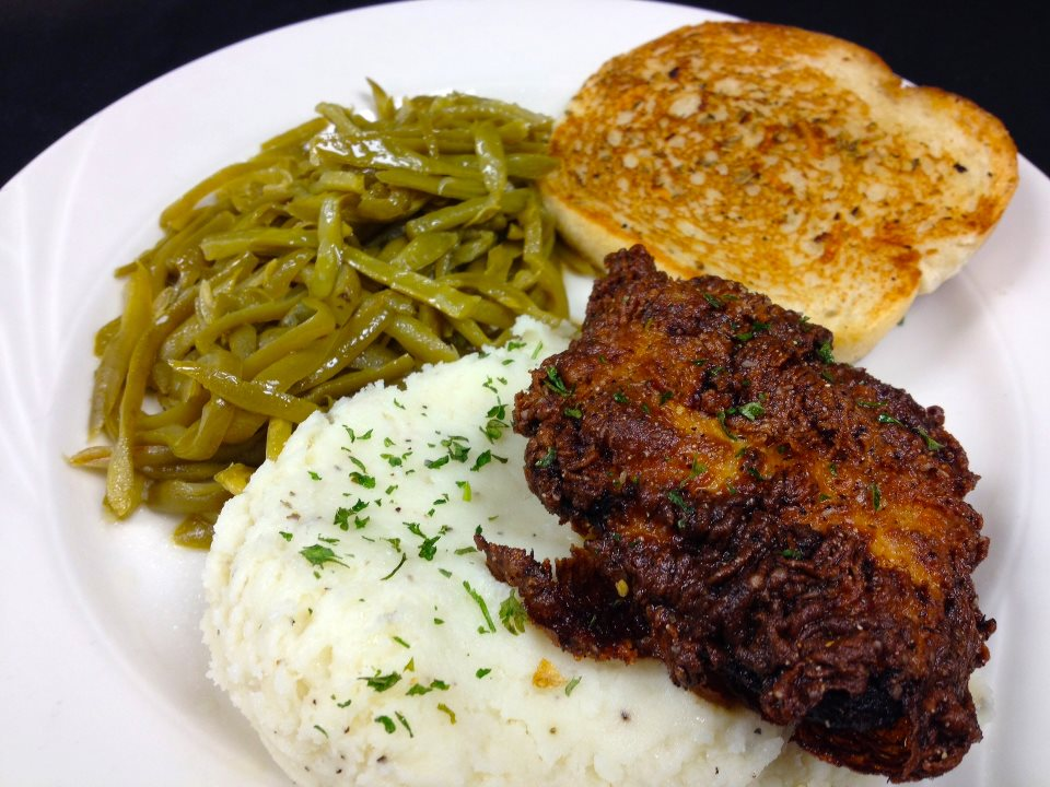 Fried chicken over mashed potatoes with string beans and garlic toast