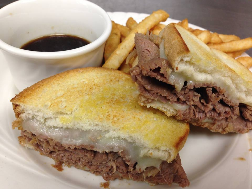 Roast beef sandwich with cheese on toast bread with fries and side of au jus