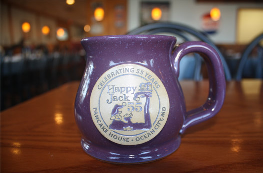 Purple coffee mug with Happy Jack Pancake House Ocean City, MD branding. Celebrating 55 years