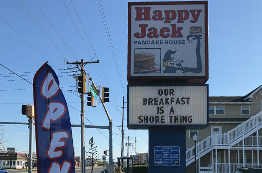 Happy Jack Pancake House sign outside the business with a marquee sign below. Our breakfast is a shore thing