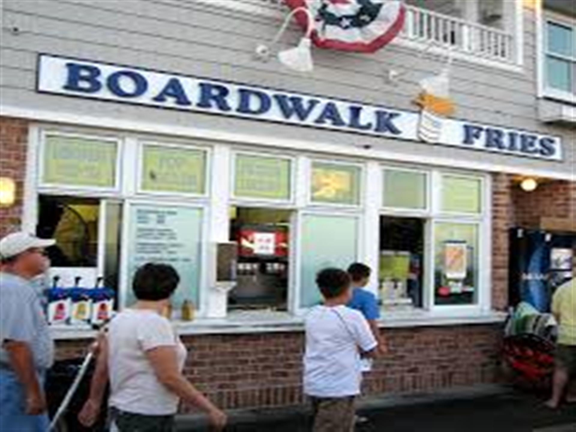 People wa;lking in front of  the Exterior of Boardwalk Fries Building