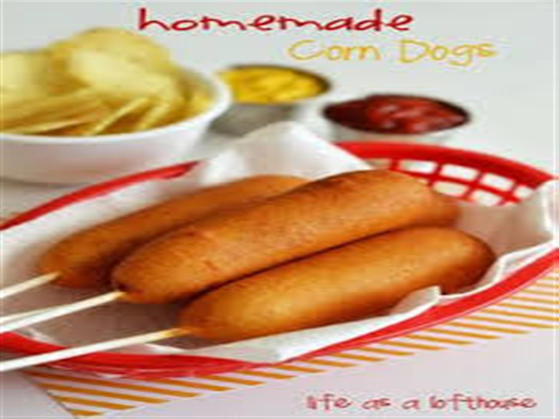3 homemade corn dogs in a basket with mustard and ketchup dipping sauces.