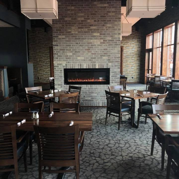 Interior dining area with wooden chairs with utensils and tables and a fireplace in a stone wall