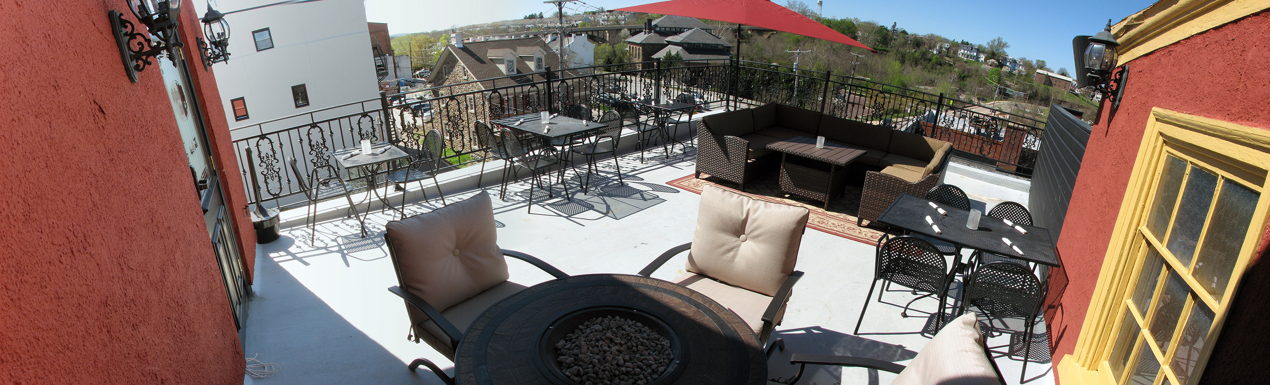 Mollys Rooftop patio with multiple tables, chairs, and wicker furniture.