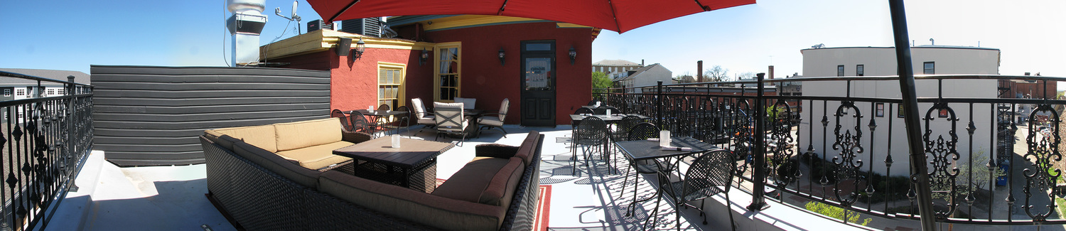 Mollys Rooftop patio with multiple tables, chairs, and wicker furniture. Adjacent buildings and views are shown.