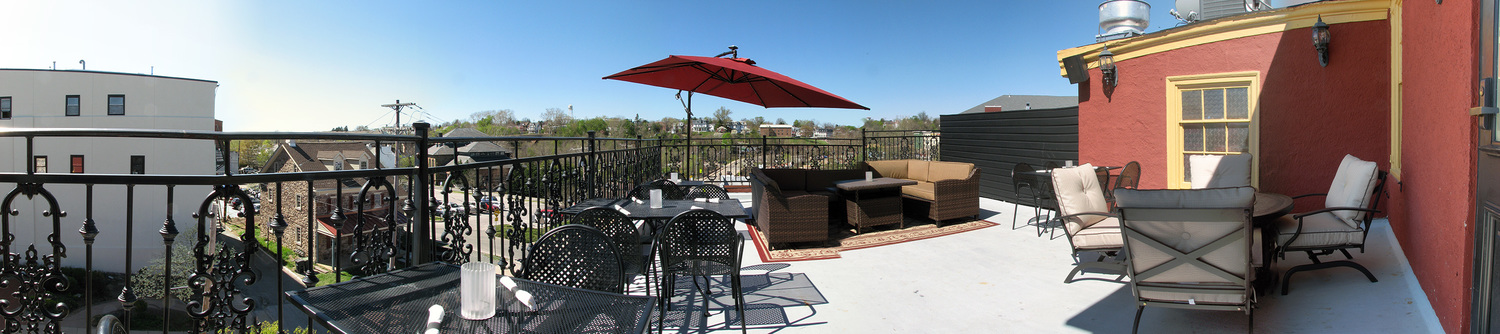 Mollys Rooftop patio with multiple tables, chairs, and wicker furniture. Adjacent views and buildings are shown.