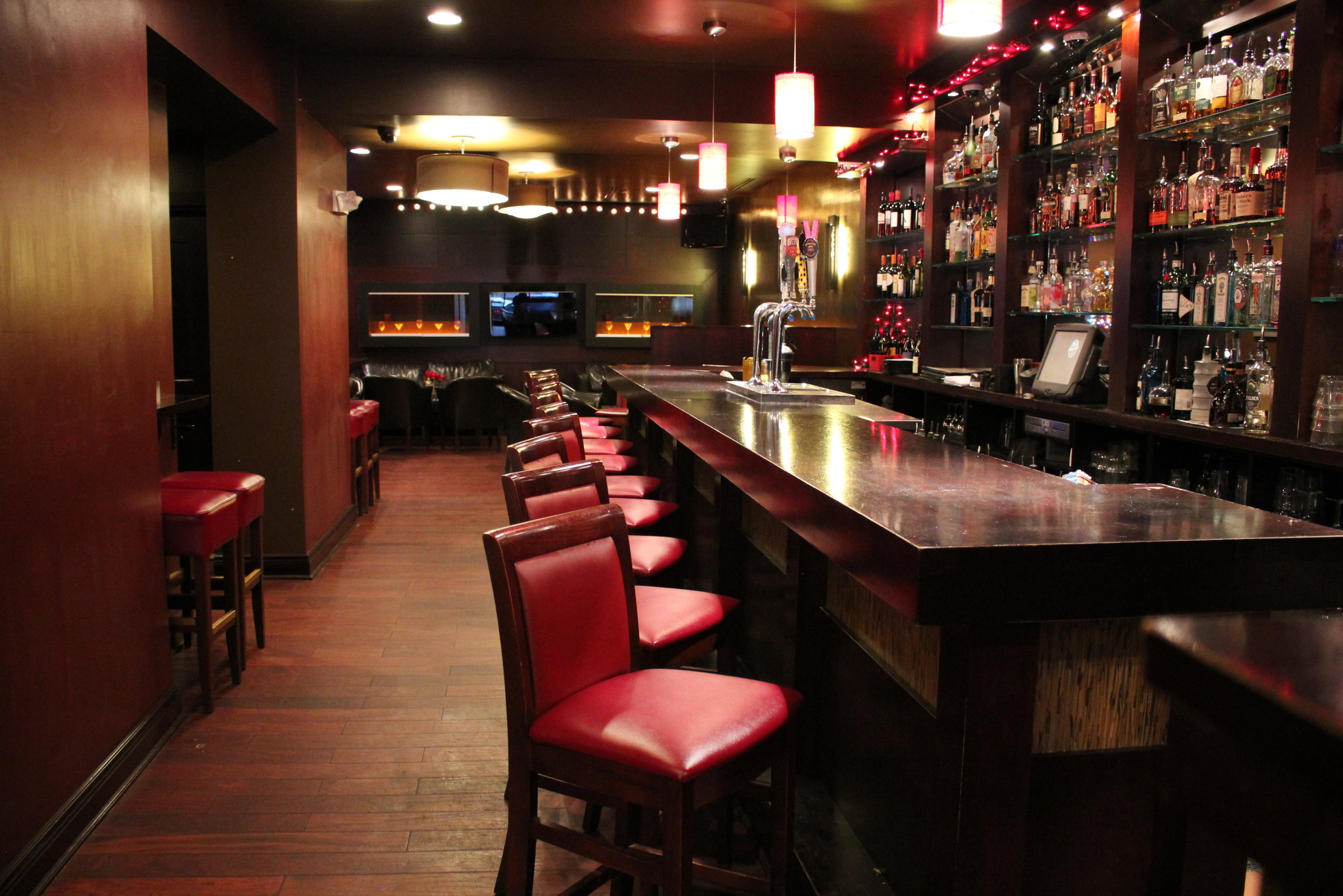 Bar in fenix room showing bottles on shelves and red chairs in front of bar.