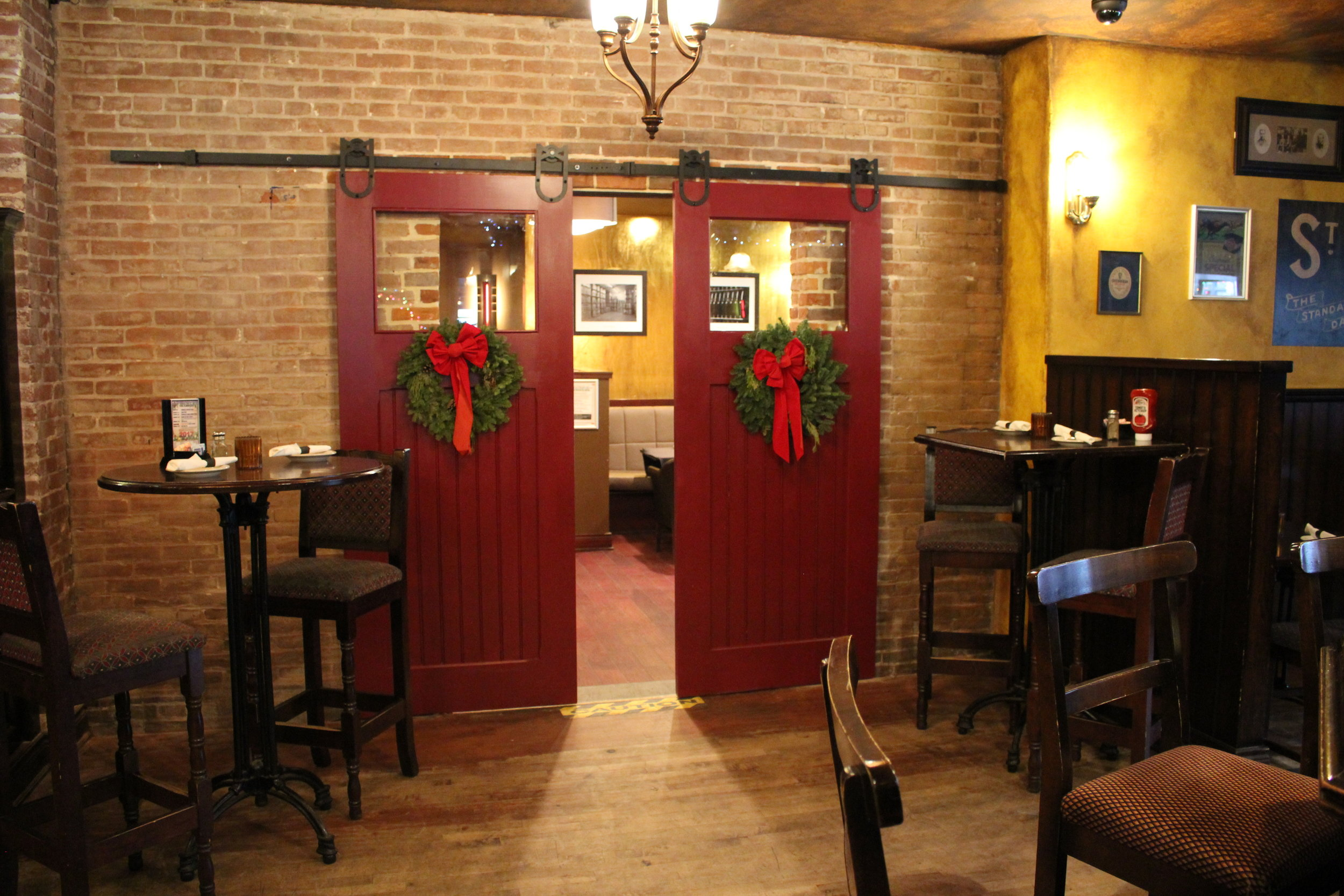 Entrance to the fenix room showing red wooden doors with wreaths