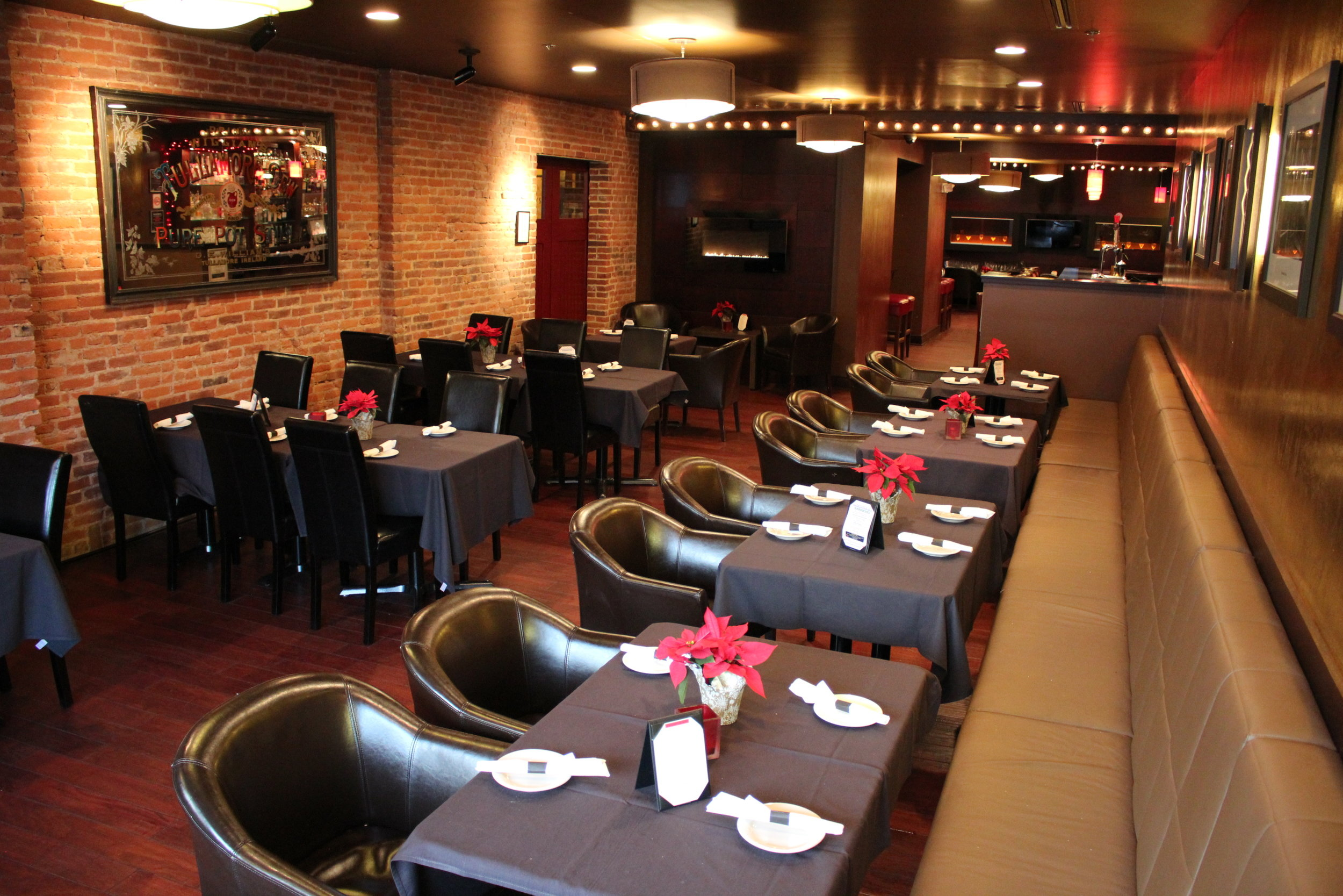 Full view of the fenix room with brick walls, brown-clothed tables and dark chairs.