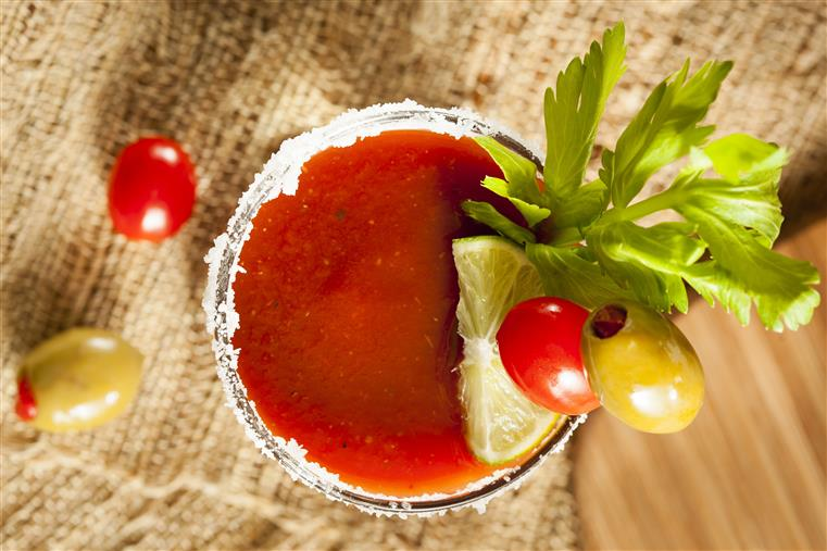 Top view of a Bloody Mary with olives, celery and lime.