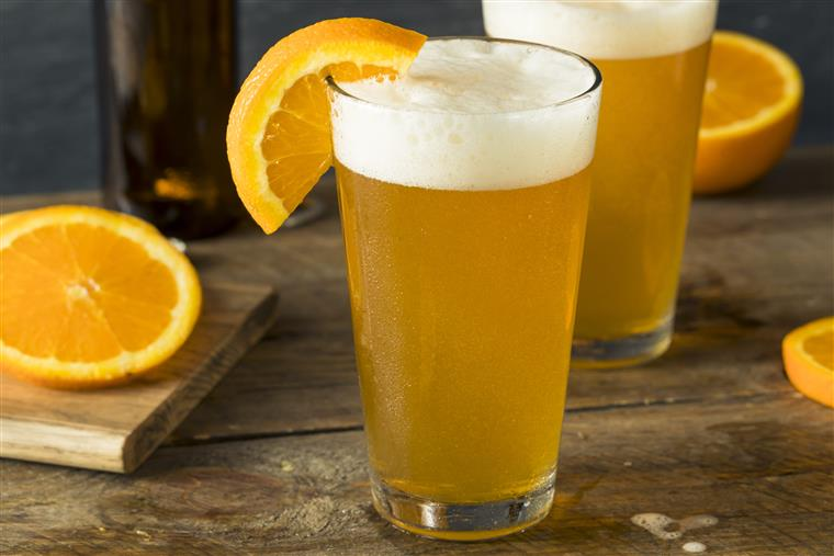 Two pints of Blue Moon beer with orange slice for garnish.