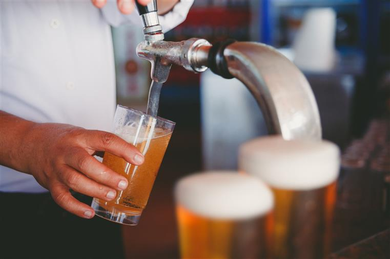 Bartender pouring three draft beers.