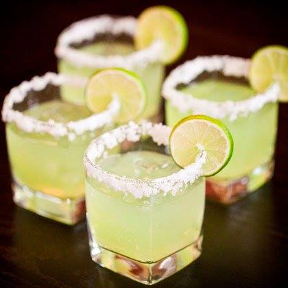Salt rimmed margarita in square glasses garnished with a lime