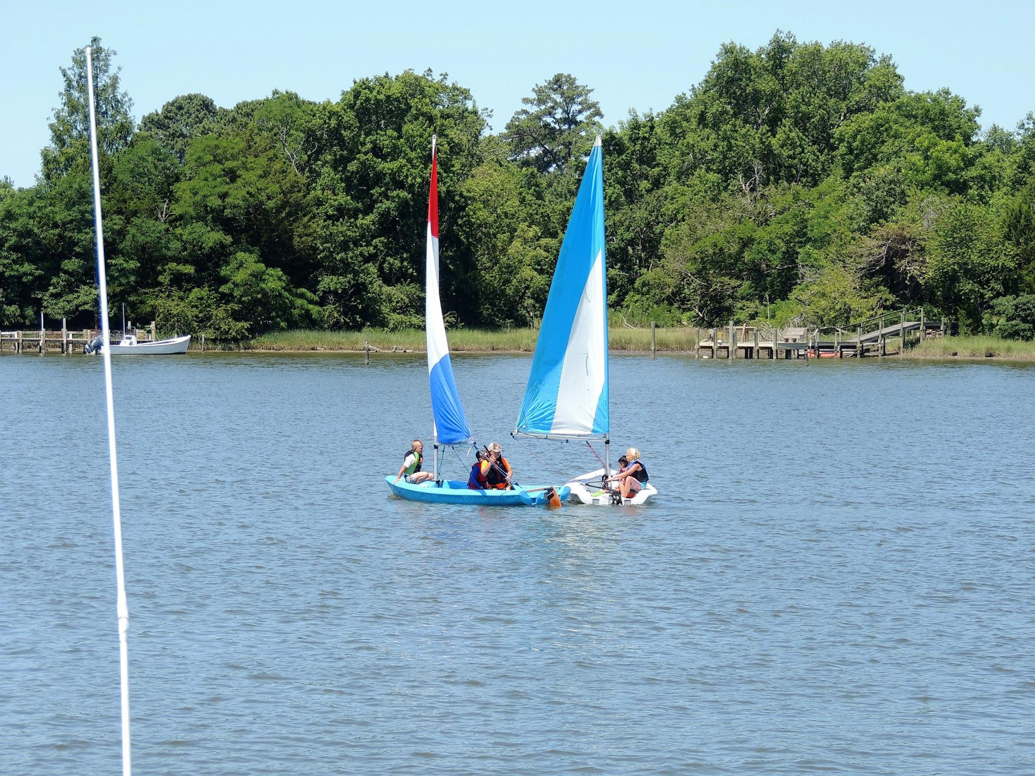 Two sailboats out on the water with people wearing life vests