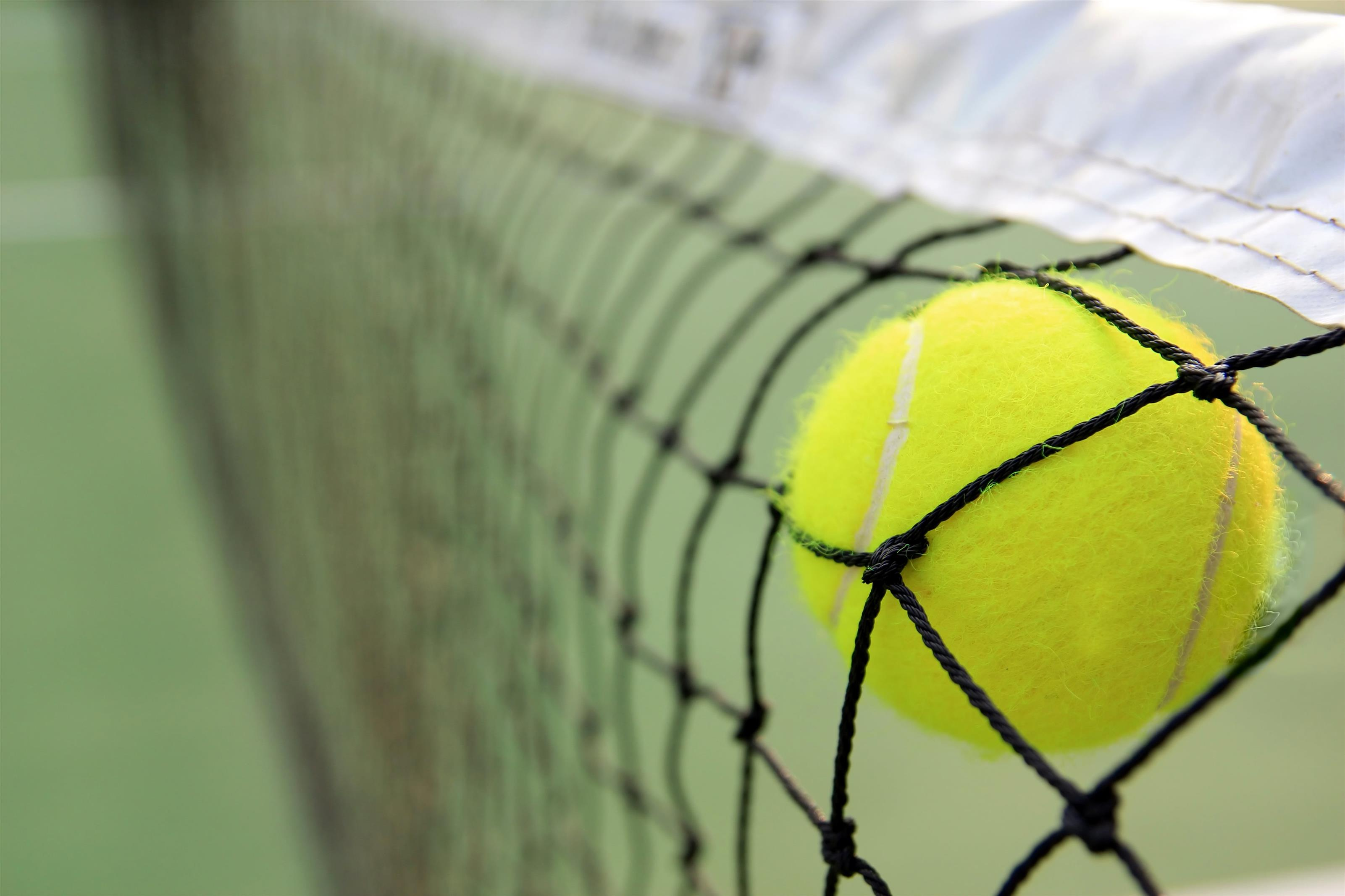 Tennis ball being caught in netting on a tennis court