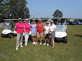Female golfers standing in front of golf carts on a course