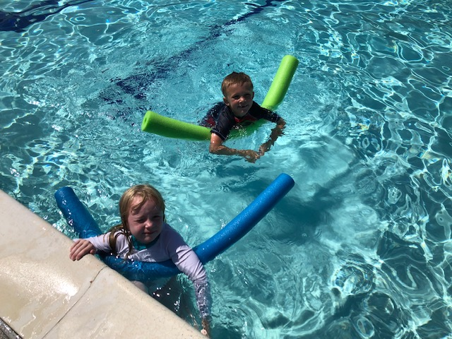 Children swimming in a pool with pool noodles