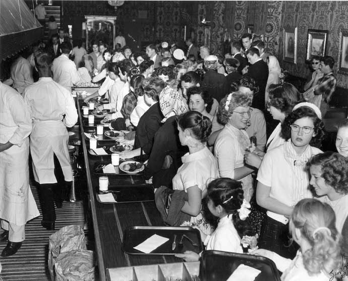 Black and white photo of people in crowded restaurant