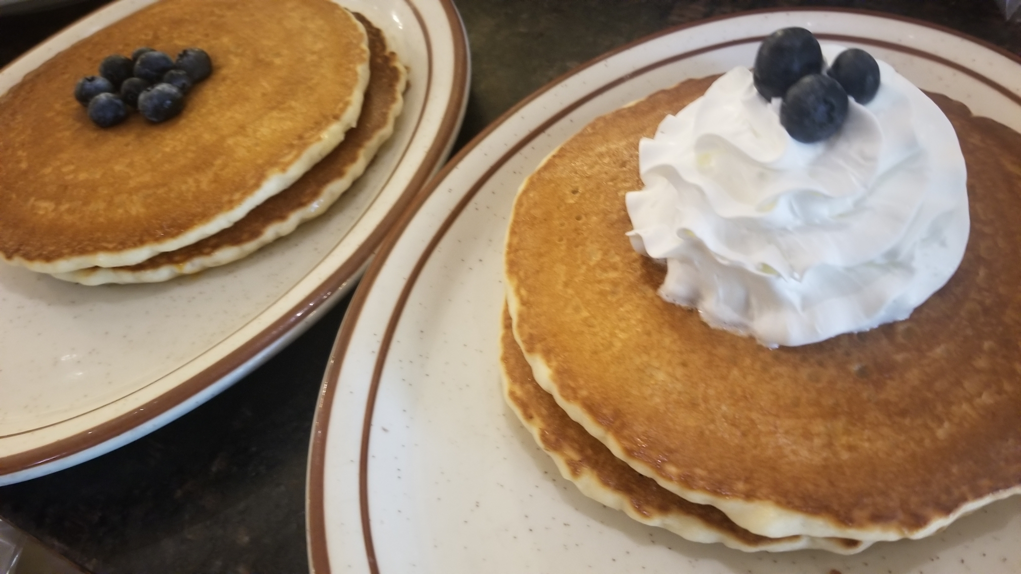 Fluffy pancakes on white plate topped with whipped cream and blueberries