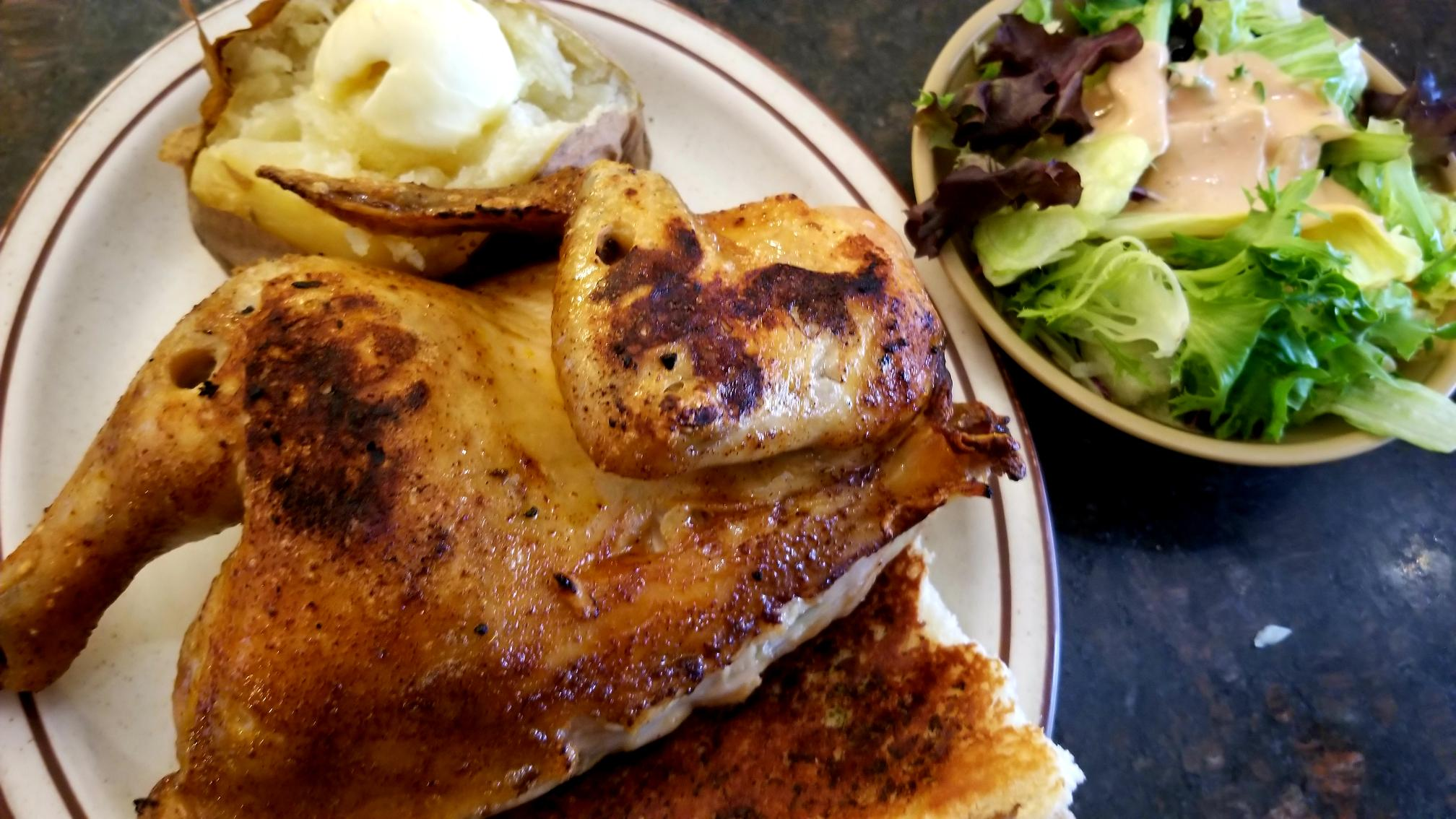 Golden browned whole chicken on white plate with baked potato and salad