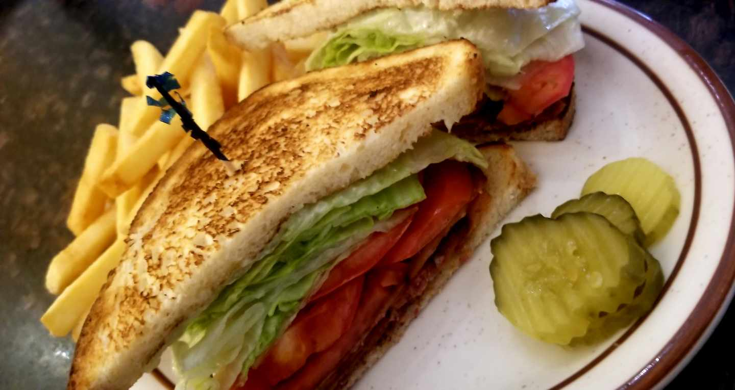 Toasted BLT on white plate with toothpick in middle next to fries
