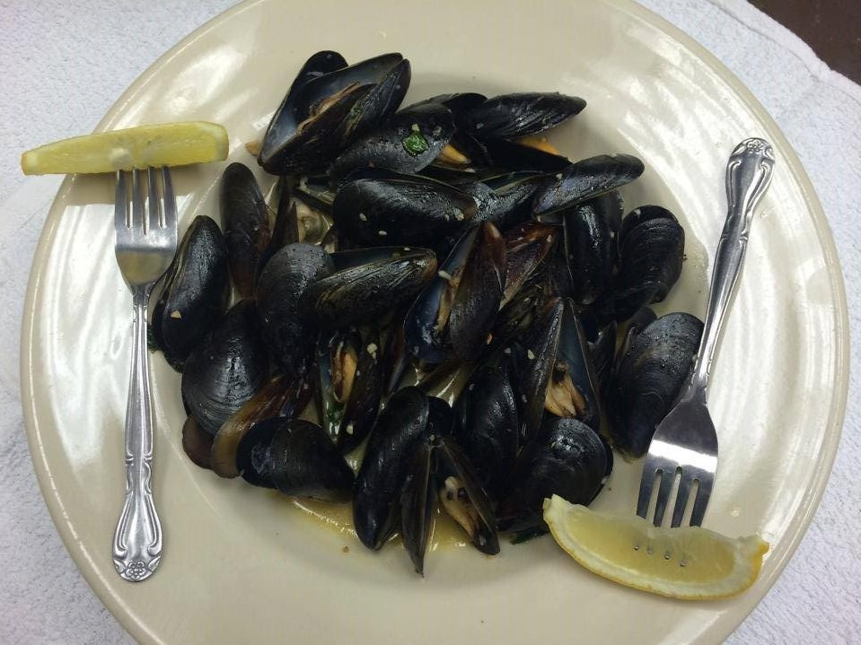 Mussles on a plate with forks and lemon