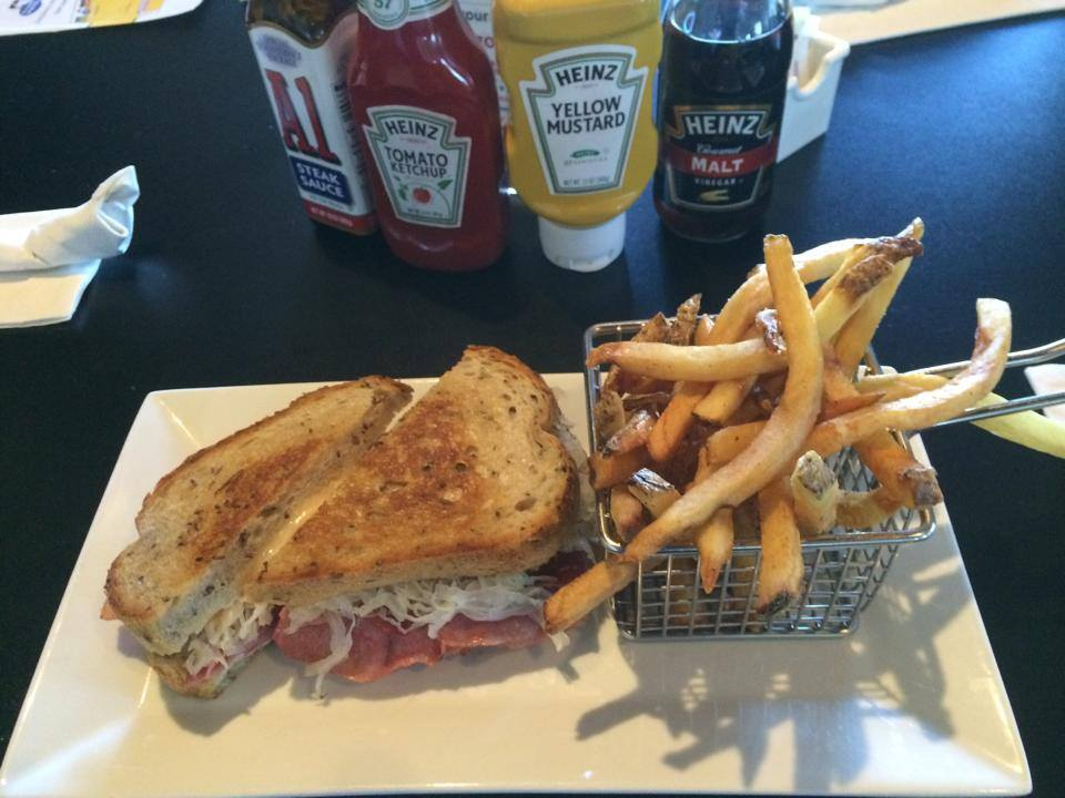 NY reuben on a plate with fries and assorted condiments