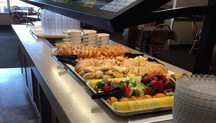 Breakfast buffet with donuts, croissants, and fresh fruit.