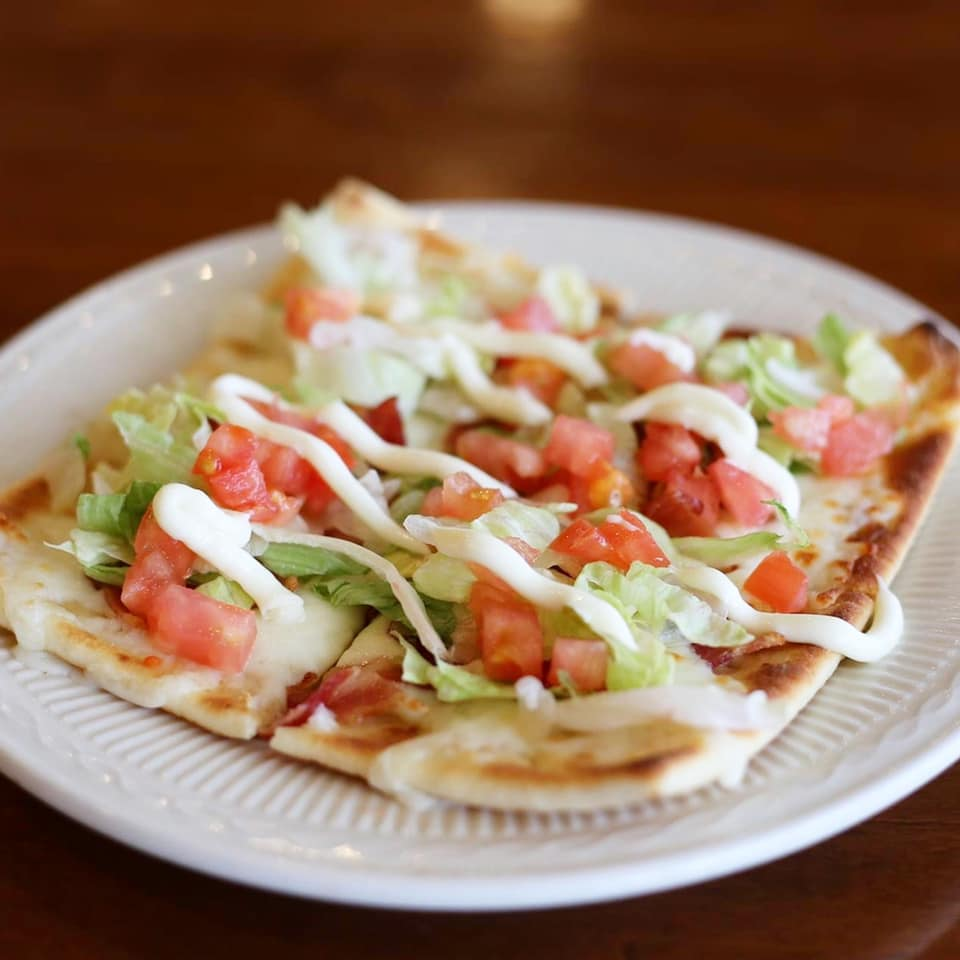 flatbread with lettuce, tomatoes and a sauce on a plate