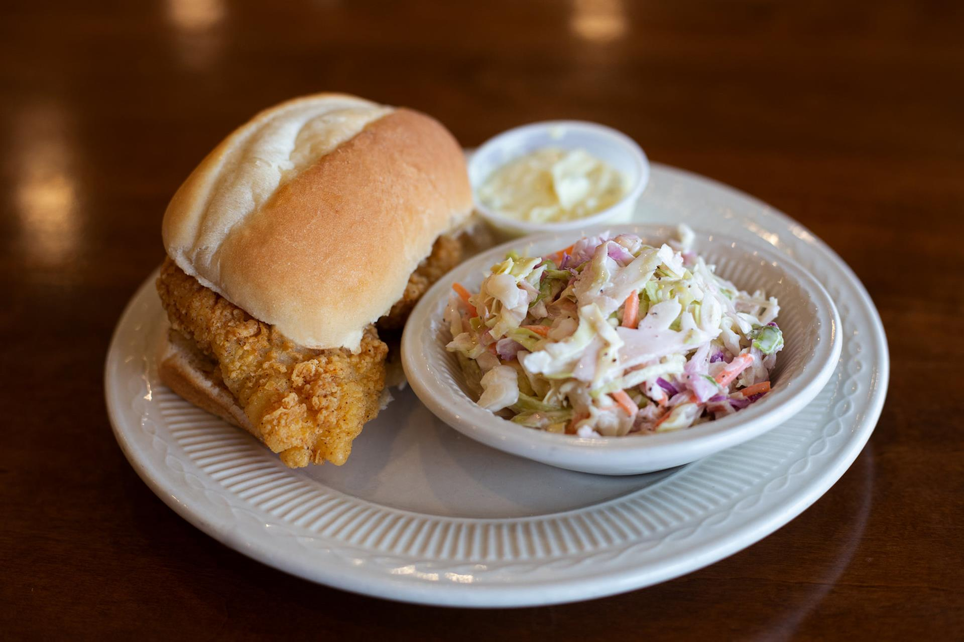 fried chicken sandwich on a bun with a side of coleslaw