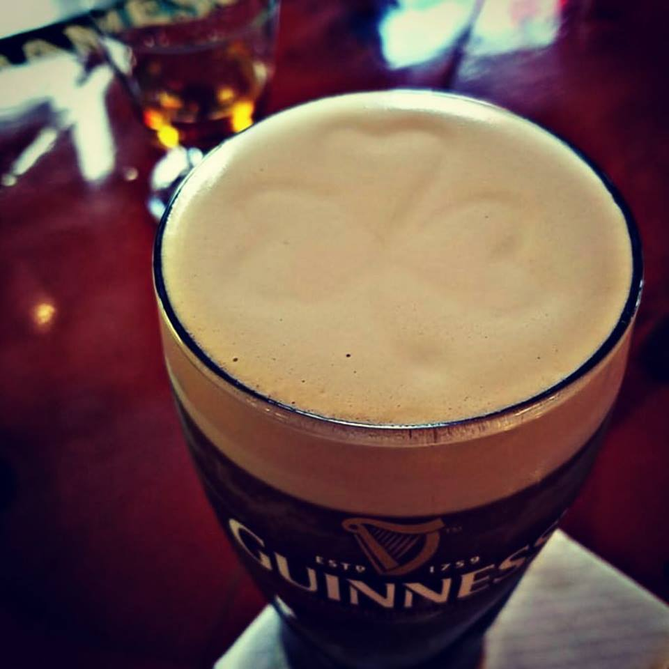 Top down view of a Guinness beer. in the foam is a shamrock.