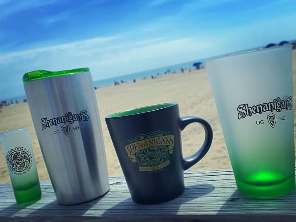 Assorted Shenanigan's branded cups, glasses and mugs on a wood ledge with a beach background