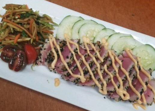 Ahi tuna with a spicy sauce drizzle and cucumber and mixed veggie salad
