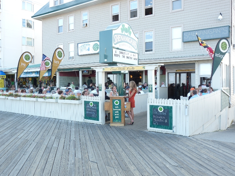 Outside patio area from the boardwalk of Shenanigan's Irish Pub filled with customers sitting at tables