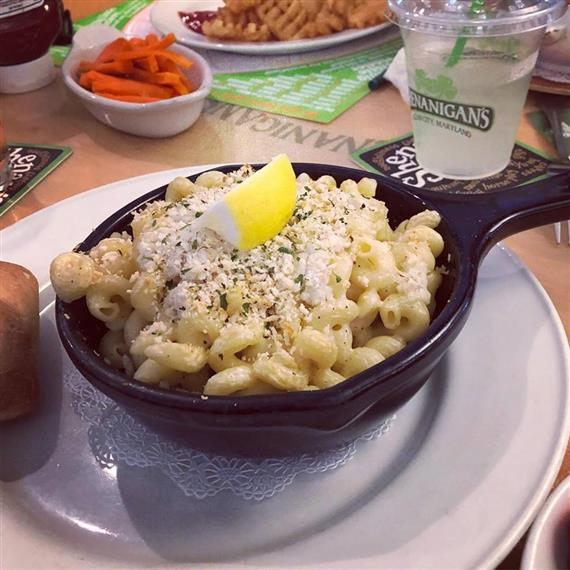 mac and cheese skillet topped with bread crumbs and a lemon wedge. Assorted appetizers in the background on the table.