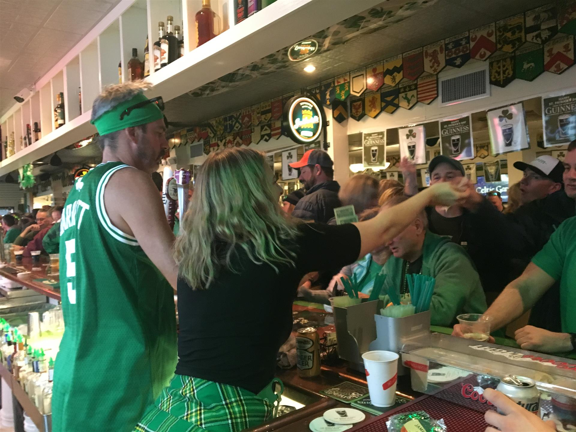View from behind the crowded bar on St. Patrick's Day 2018. Two bartenders serving drinks.