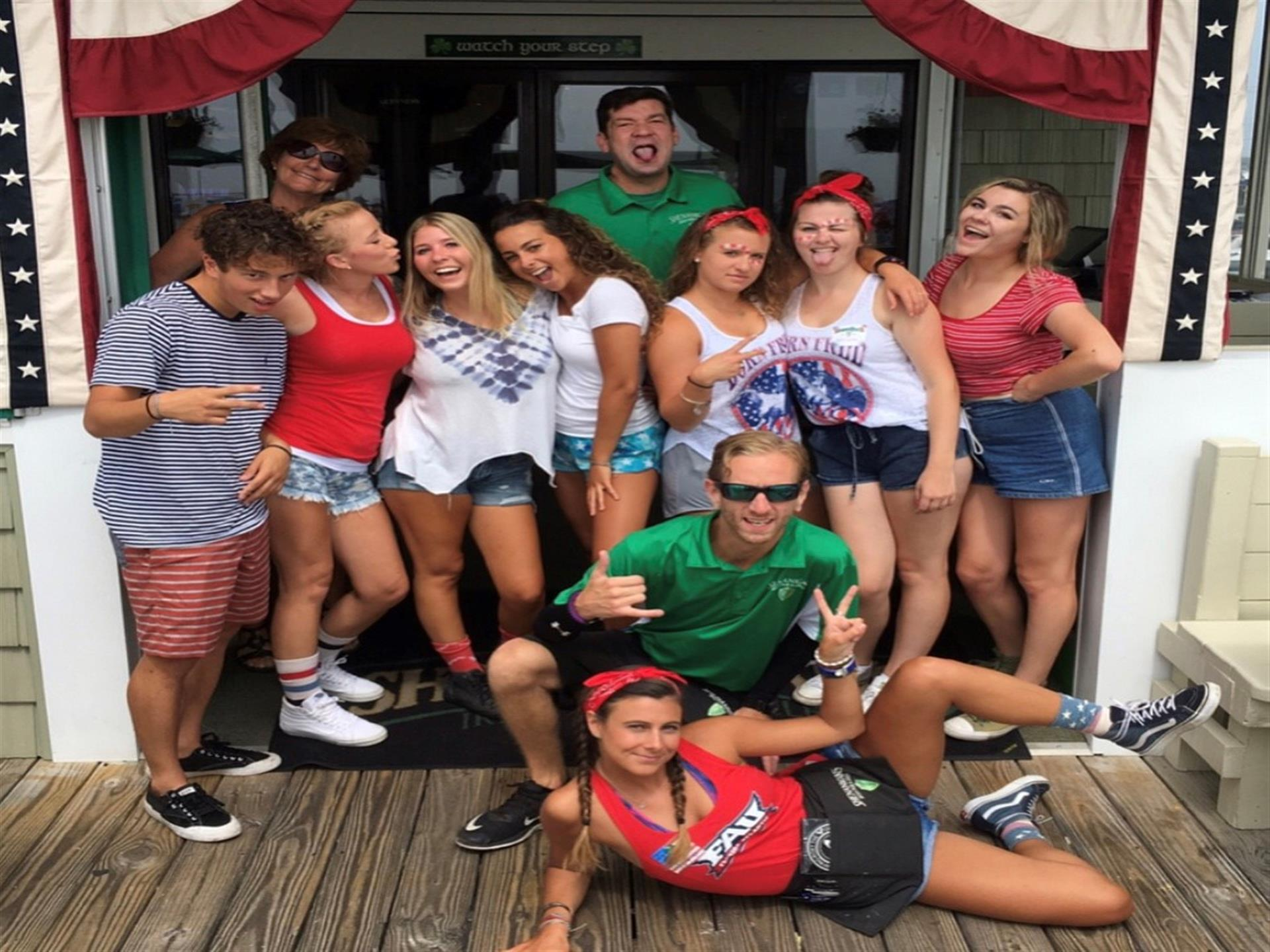 Staff of Shenanigan's dressed in red, white and blue and standing outside on the boardwalk.