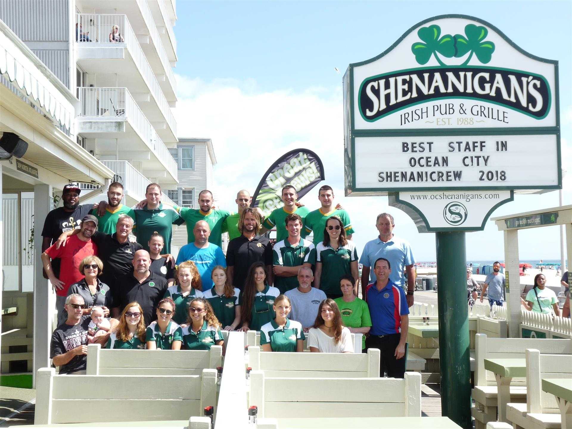 Staff of Shenanigans group photo outside on the boardwalk by the Shenanigan's sign.