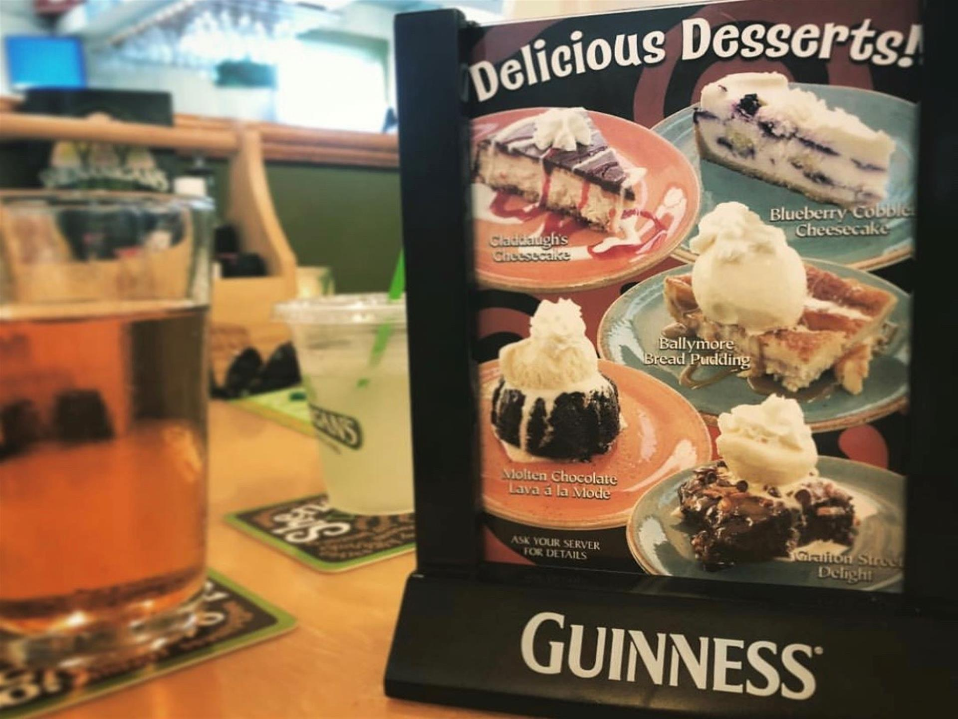 Table tent showing Delicious Desserts next to a glass of beer.