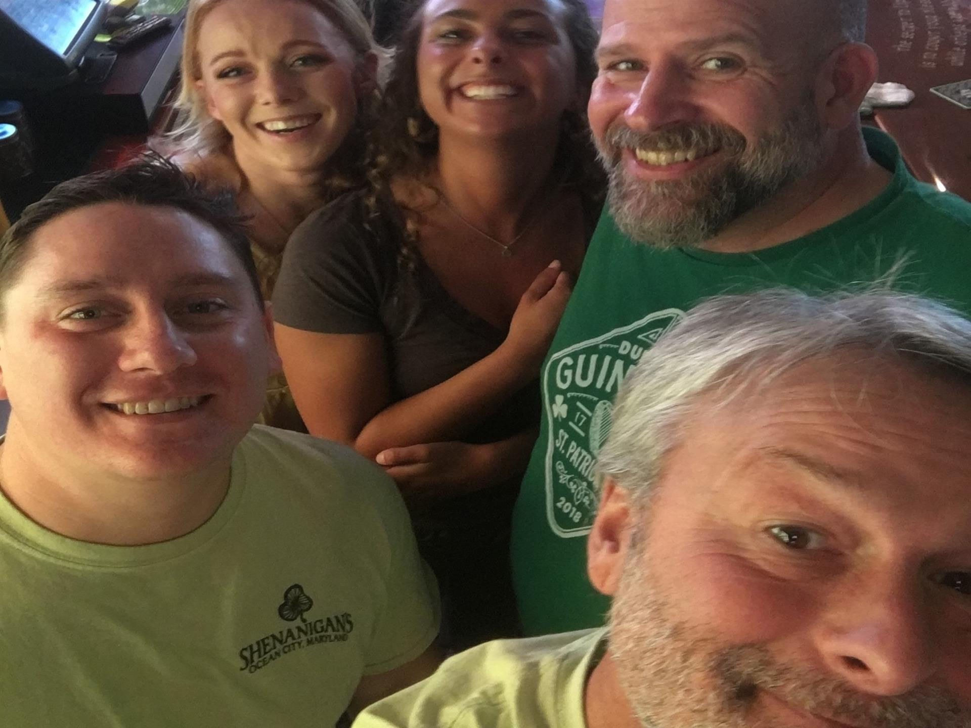 Five Shenenigan's staff members smiling and taking a selfie.