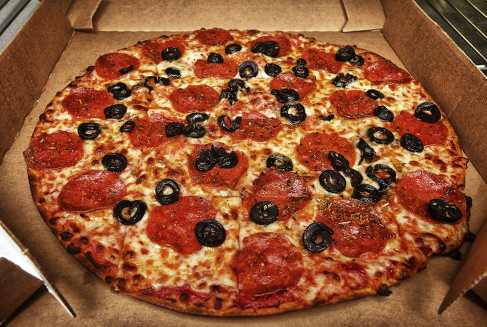 Pepperoni pizza with black olives in a pizza box