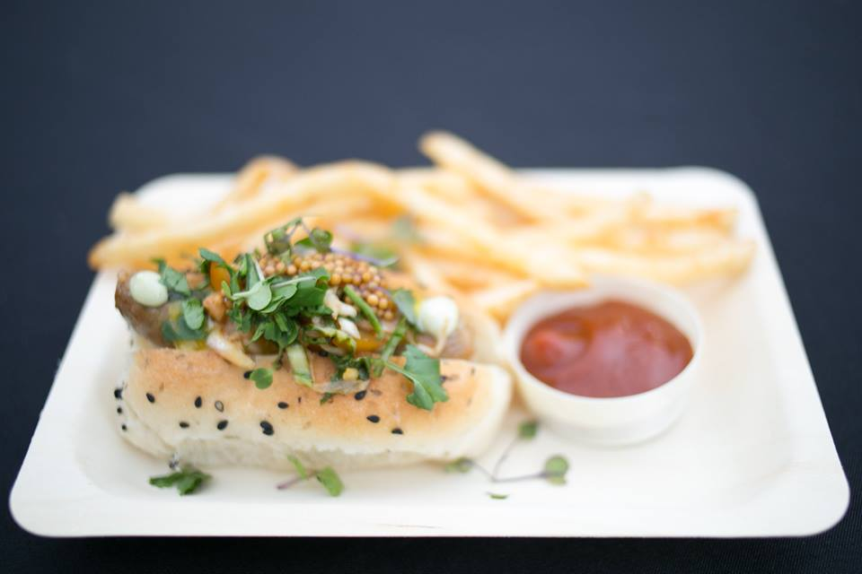 piece of fish with sesame seeds and herbs with french fries and a dish of ketchup on a plate