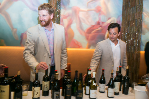 Two men standing behind a table with bottles of wine