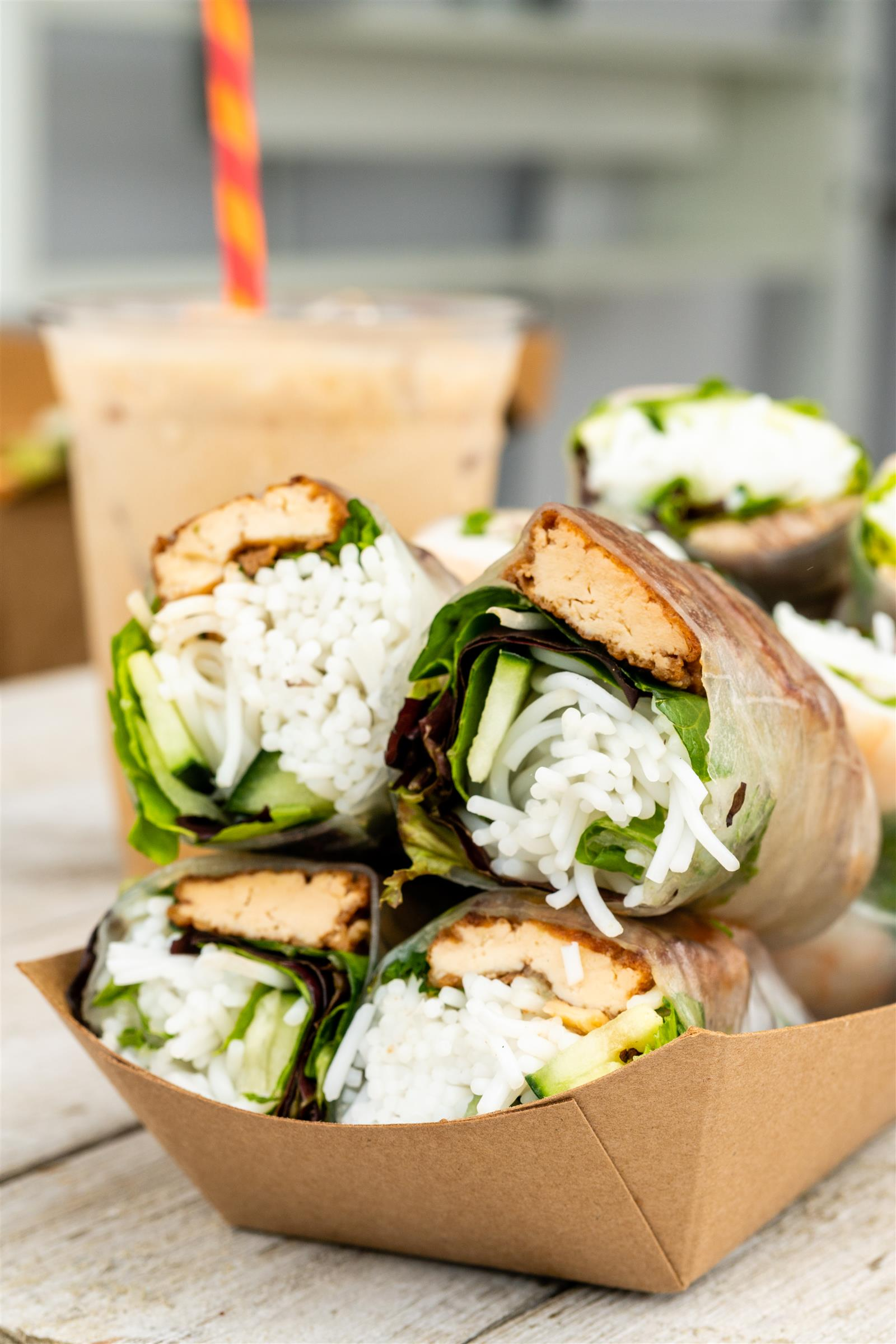 Tufu, lettuce, cucumber, and white rice wrap in a cardboard box on a white wooden table infront of iced beverage