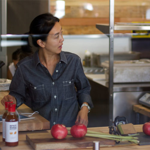 MONICA WONG-CEO in denim shirt standing at wooden table looking to the right
