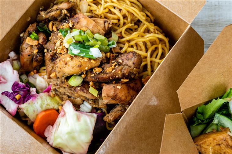 Vietnamese bento box with juicy marinated Chicken on top of yellow noodles topped with vegetable slaw