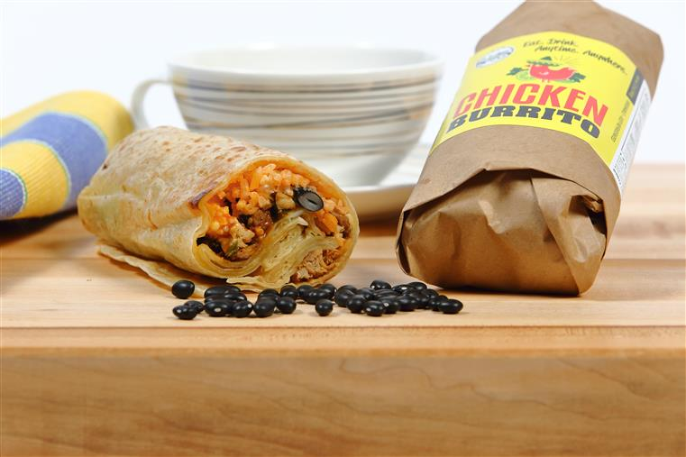 Grab 'n Go chicken burrito on a wood table with teacup and blue and yellow napkin in the background.