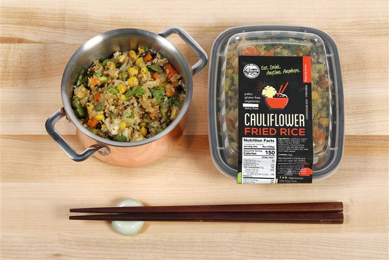 Grab n' Go cauliflower fried rice on a wood table next to a bowl of cauliflower fried rice with a set of chopsticks.