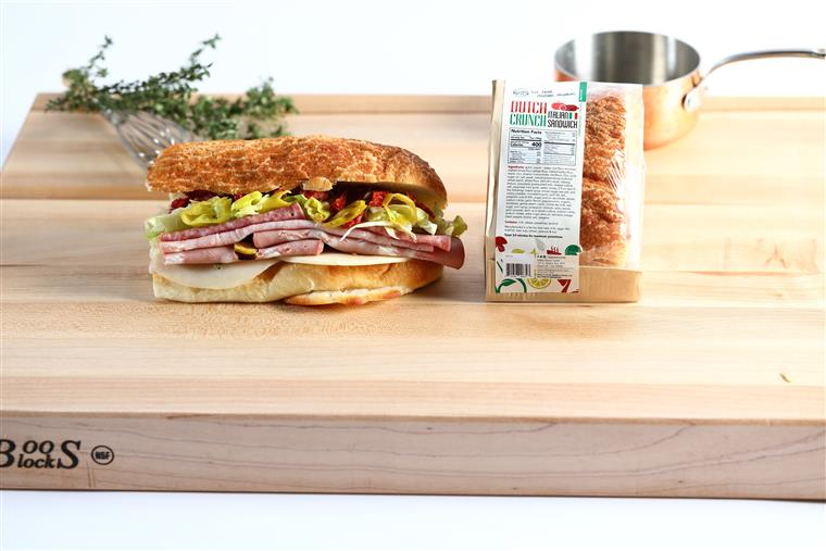 Grab 'n Go Dutch Crunch Italian Sandwich on a wood table. Herbs and small metal pot in the background.